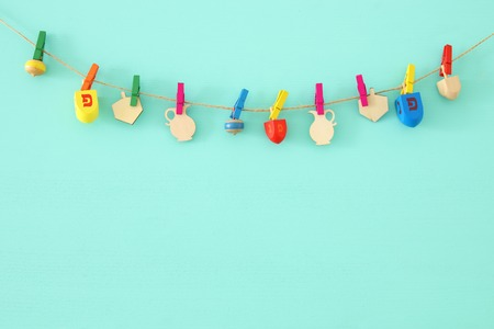 Image of Jewish holiday Hanukkah with wooden dreidels collection (spinning top) over mint background