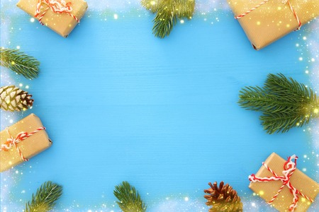 Christmas background with pine cones, fir branches and gifts over wooden blue background. Flat lay, top view