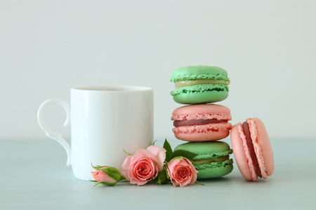White vintage cup of coffee and colorful macaron or macaroon over pastel wooden table 免版税图像