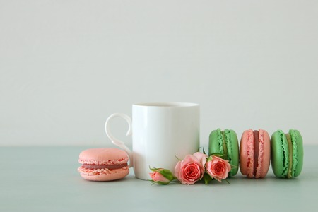 White vintage cup of coffee and colorful macaron or macaroon over pastel wooden table 版權商用圖片