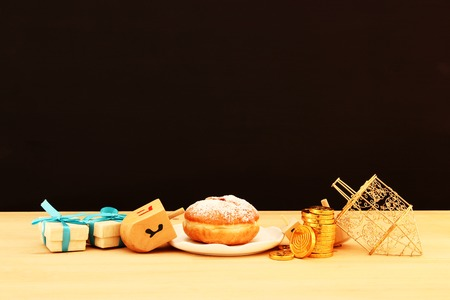 Image of Jewish holiday Hanukkah with traditional doughnut and spinning top on the table
