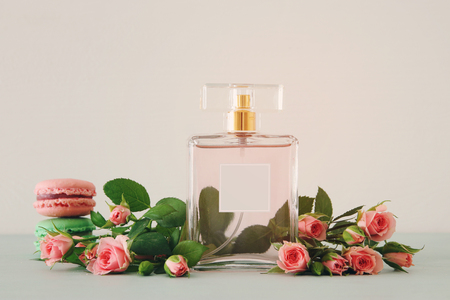 Image of perfume bottle with rose petals flowers and macaroon over pastel table Foto de archivo