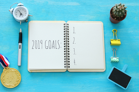 Top view 2019 goals list with notebook over wooden desk