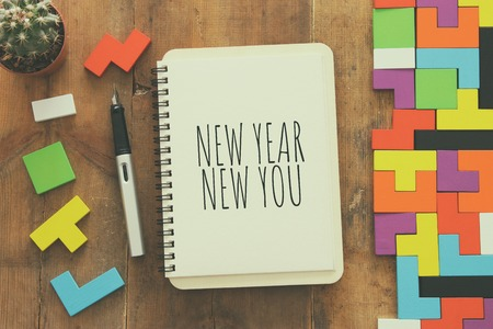 Top view of notebook and text NEW YEAR NEW YOU over wooden desk