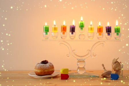 image of jewish holiday Hanukkah background with crystal menorah (traditional candelabra) and colorful oil candles Archivio Fotografico