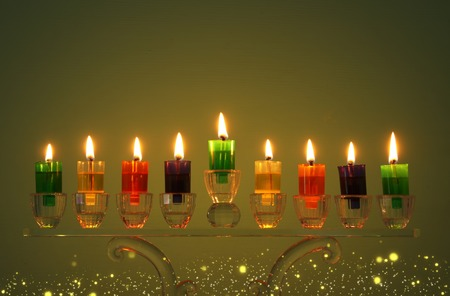 image of jewish holiday Hanukkah background with crystal menorah (traditional candelabra) and colorful oil candles Banque d'images