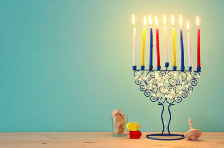 image of jewish holiday Hanukkah background with menorah (traditional candelabra) and colorful candles. Stock Photo