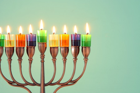 image of jewish holiday Hanukkah background with menorah (traditional candelabra) and colorful oil candles