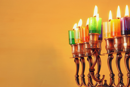 image of jewish holiday Hanukkah background with menorah (traditional candelabra) and colorful oil candles. Selective focus