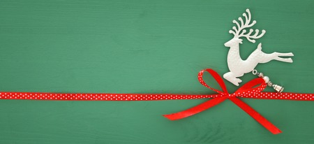 Christmas background with red silk traditional ribbon and white deer