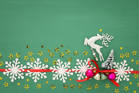 Christmas background with red silk traditional ribbon, white deer, evergreen tree and jingle bells