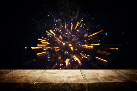 mesa de madera rústica frente a luces brillantes estallan. desenfocado Foto de archivo