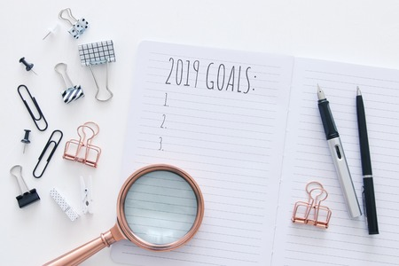 Top view 2019 goals list with notebook over white wooden desk