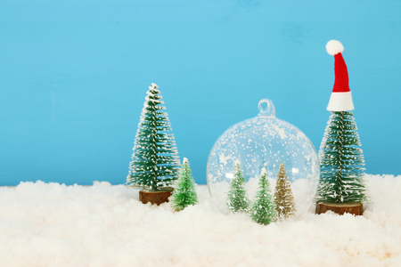 image of christmas trees inside glass ball over snowy wooden table Stockfoto