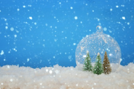 image of christmas trees inside glass ball over snowy wooden table 免版税图像