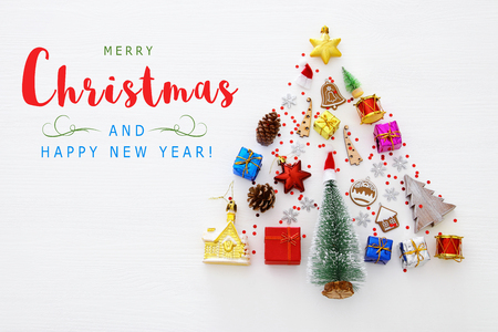 Top view image of festive decorations in shape of christmas tree over white wooden background. Flat lay Stock fotó