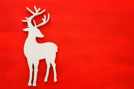 Top vie image of white wooden christmas deer over red background. Flat lay.