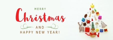 Top view image of festive decorations in shape of christmas tree over white wooden background. Flat lay 免版税图像