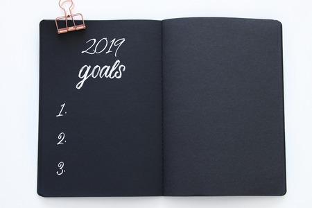 Top view 2019 goals list with notebook over wooden white desk