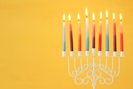 image of jewish holiday Hanukkah background with menorah (traditional candelabra) and colorful candles 免版税图像