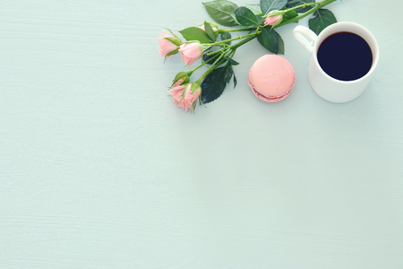 Top view image of white cup of coffee and colorful macaron or macaroon over pastel wooden background