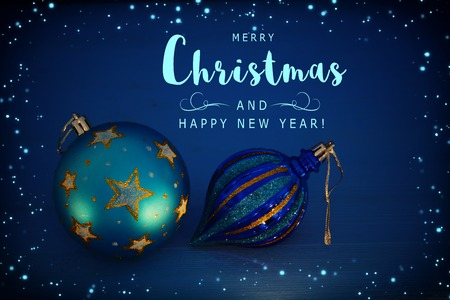 Image of Christmas festive tree ball decoration with gold stars in front of blue background