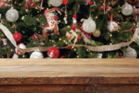Empty table in front of christmas tree with decorations background. For product display montage 免版税图像