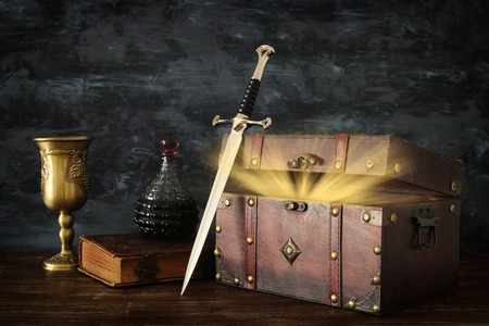 Low key image of open chest with treasure, wine cup, antique old book and sword. Fantasy medieval period