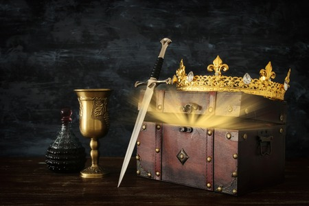 Low key image of beautiful queen/king crown, open chest with treasure and sword. Fantasy medieval period Imagens
