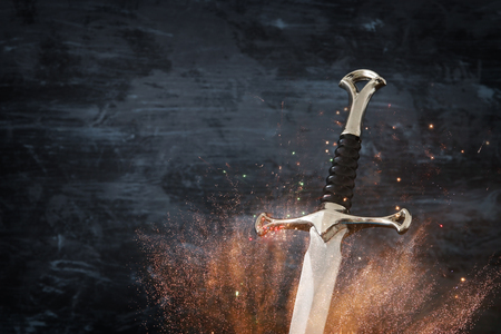 low key image of silver sword with fire sparks. fantasy medieval period