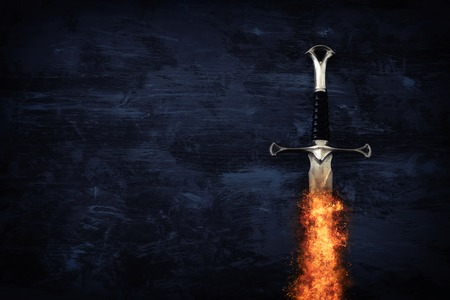 low key image of silver sword in the flames of fire. fantasy medieval period Stock Photo