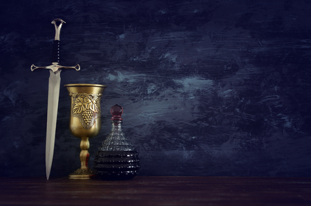 low key image of wine cup and sword. fantasy medieval period Banque d'images