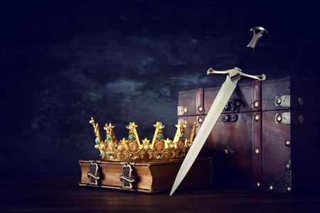 low key image of beautiful queen/king crown over antique book, chest and sword. fantasy medieval period
