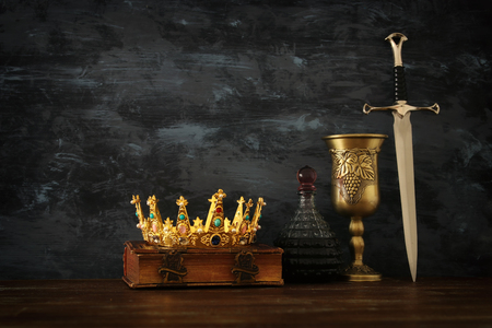low key image of beautiful queenking crown, wine cup and sword. fantasy medieval period