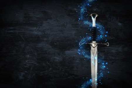 low key image of silver sword with magical lights. fantasy medieval period