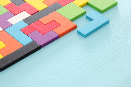 A colorful square tangram puzzle, over wooden table