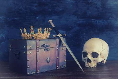 low key image of beautiful queenking crown over old chest , human skull and sword. fantasy medieval period Stock Photo