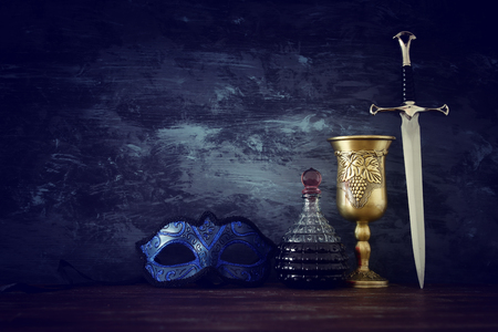 low key image of wine cup, mysterious mask and sword. fantasy medieval period