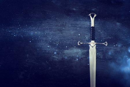 low key image of silver sword. fantasy medieval period. Glitter overlay