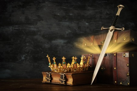 low key image of beautiful queenking crown, open chest with treasure and sword. fantasy medieval period