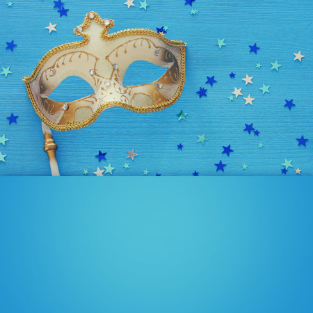 carnival party celebration concept with elegant gold mask on stick over blue wooden background and stars. Top view