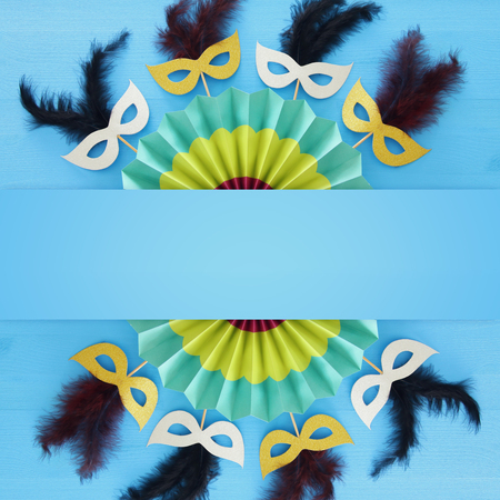 carnival party celebration concept with masks and colorful fan over blue wooden background. Top view - Image
