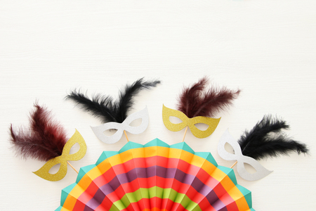 carnival party celebration concept with masks and colorful fan over white wooden background. Top view Stock Photo