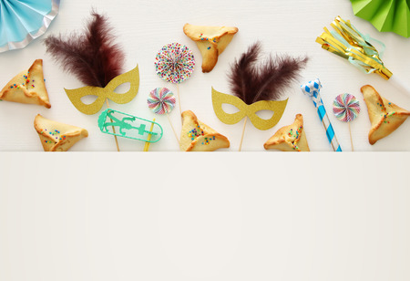 Purim celebration concept (jewish carnival holiday) over white wooden background. Top view