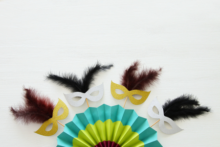 carnival party celebration concept with masks and colorful fan over white wooden background. Top view - Image Stock Photo