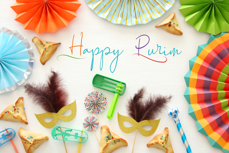 Purim celebration concept (jewish carnival holiday) over white wooden background. Top view - Image