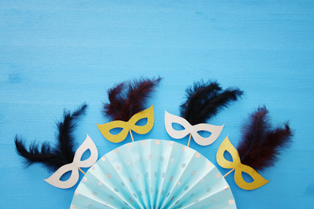 carnival party celebration concept with masks and colorful fan over blue wooden background. Top view Stock Photo