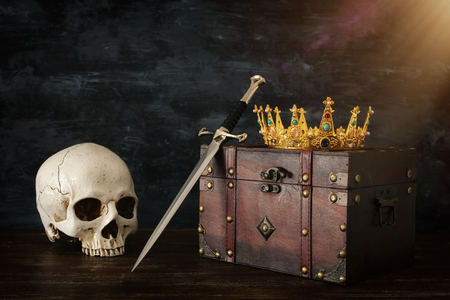 Low key image of beautiful queenking crown over old chest, human skull and sword. Fantasy medieval period Stock Photo