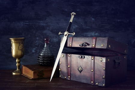 Low key image of open chest, wine cup, antique old book and sword. Fantasy medieval period