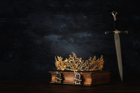 Low key image of beautiful queenking crown and sword. Fantasy medieval period